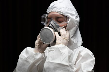 Woman wearing gloves with biohazard chemical protective suit and mask.