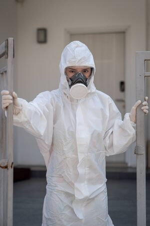 Woman wearing gloves with biohazard chemical protective suit and mask.with unhappy face. Opening an iron gate. Reklamní fotografie