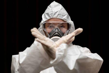 Frau mit Handschuhen mit chemischem Schutzanzug und Maske für biologische Gefahrenstoffe. Mit unglücklichem Gesicht. Frau hält zwei Hände vor sich, Stoppschild, Stoppschild.