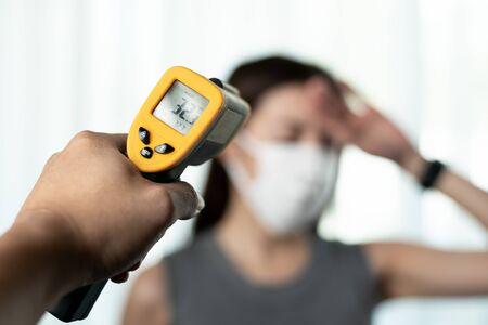 Femme se sentant malade portant un masque de protection. Avec le contrôle manuel de la sécurité aux portes, utilisez un thermomètre numérique pour vérifier la température.