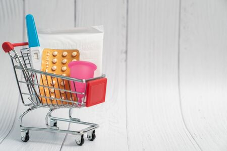 Pregnancy test, Birth control pill and sanitary napkin pad on Shopping cart. Concept for contraceptive. Stock Photo