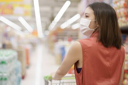 covid-19 spreading outbreak. Woman in medical protective mask panic buying food. Fear of coronavirus. 版權商用圖片