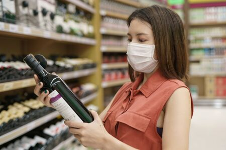 covid-19 spreading outbreak. Woman in medical protective mask panic buying wine. Fear of coronavirus.