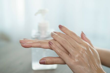 Female hands using wash hand sanitizer gel pump dispenser. Clear sanitizer in pump bottle, for killing germs, bacteria and virus.
