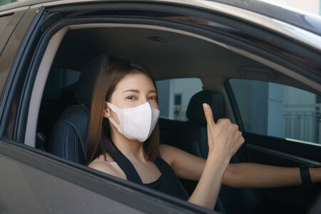 Wome wearing surgical mask in the car, for corona virus or Covid-19 protection.