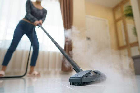 Woman washes the floor with a steam mop.