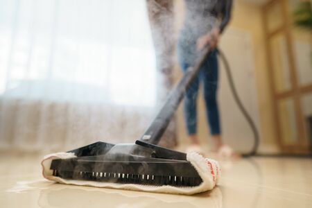 Woman washes the floor with a steam mop. Banque d'images