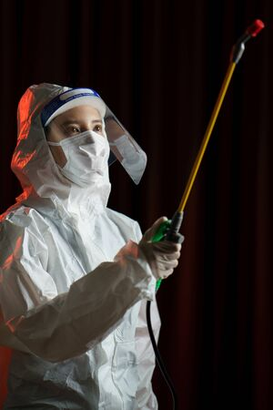 Woman in protective hazmat suit spraying disinfectant to stop spreading coronavirus or COVID-19.