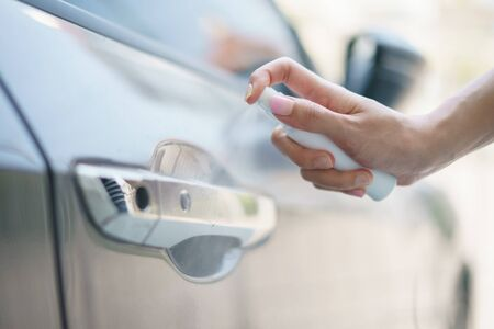 Hand hold bottle alcohol spraying disinfecting door handle of car, for corona virus or Covid-19 protection.