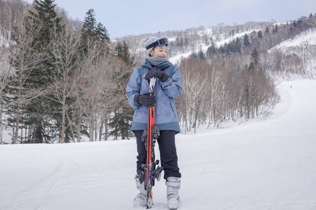 woman with ski in her hand wearing ski glasses in snow winter mountain.