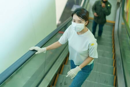 Person holding handrail of escalator in public by glove for corona virus or Covid-19 protection.