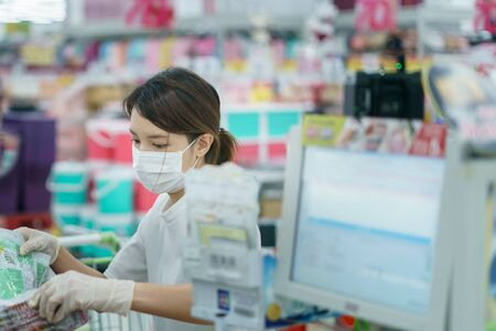 Woman protects herself from corona infection with surgical mask and gloves at cashier scanning grocery . Stockfoto