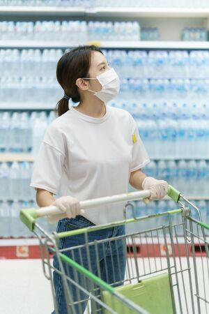 Woman wearing surgical mask and gloves, buying drinking water in supermarket. Panic shopping after coronavirus pandemic. Stockfoto