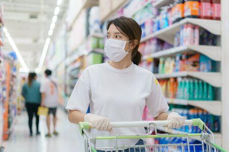 Femme portant un masque chirurgical et des gants avec un caddie, faisant ses courses pendant une pandémie de coronavirus.