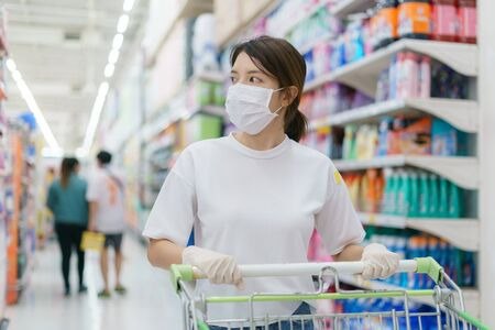 Woman wearing surgical mask and gloves with a shopping trolley, shopping during a Coronavirus pandemic.