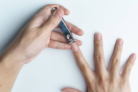 Man using nail clipper clipping her fingernails. white background