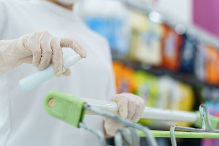Woman hand disinfecting shopping cart with alcohol spray for corona virus or Covid-19 protection.