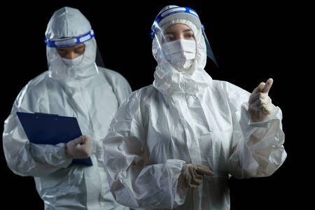 Doctor wearing PPE and face shield talking about corona/covid-19 virus laboratory report. Stock Photo