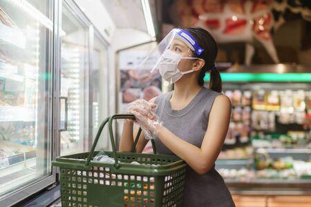 Frau mit Handschuhen, Gesichtsschutz und Maske. Panikeinkäufe während der Corona-Virus-Pandemie. Standard-Bild