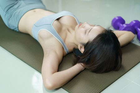 Young woman in gray sportswear exercise at home, doing abs sit ups, in quarantine during Coronavirus pandemic.