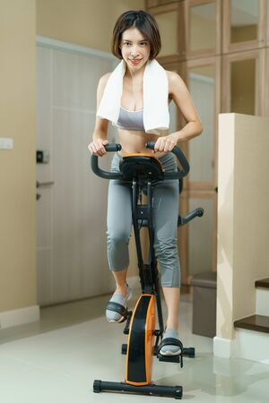 Fitness workout : woman training at home, biking exercise or Indoor cycling.