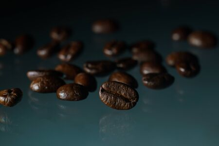Roasted coffee beans pile on glass reflection background.