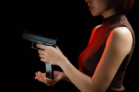 Woman hands holding and loading gun magazine in the pistol on black background. Stock fotó