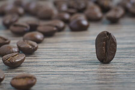 Coffee beans stands on a wooden background.