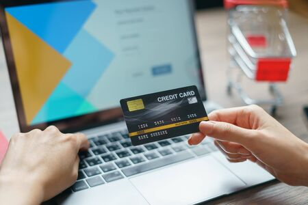 Woman hands holding and using cradit card for shopping online.
