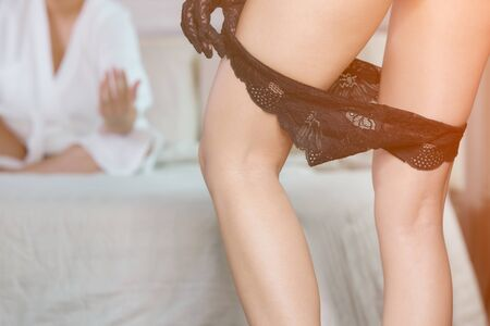 Woman taking off her panties and Man in bathrobe lying on the bed