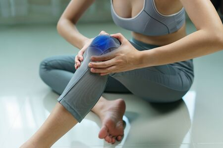 Woman holds her hands to the knee, pain in the knee highlighted in blue, medicine, massage concept.