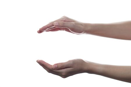 Female open cupped hands with empty between on white isolated background. Banco de Imagens