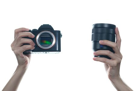 Woman hand holding camera and lens on white background.