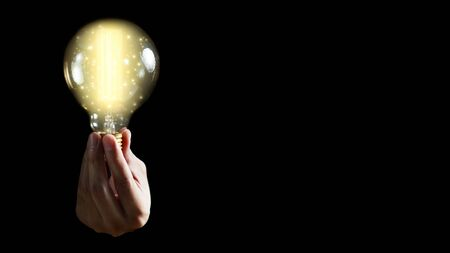 Man hand holding light bulb on black background. idea concept with inspiration.
