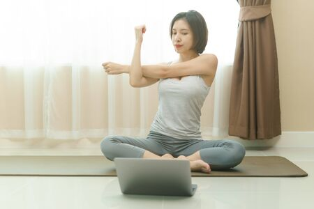 Woman warm up by stretching arms before exercises at home with laptop.