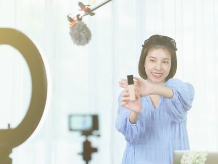 Woman vlogger holding skin care in hands, looking in camera while recording video for blog.