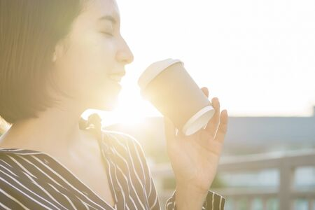 Woman holding paper coffee cup to take away in morning with sunlight.