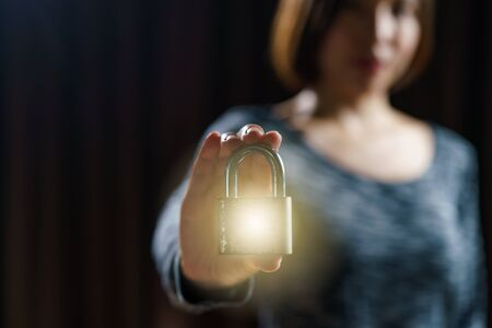 Woman holding gold master lock key is concept to lock a datas.