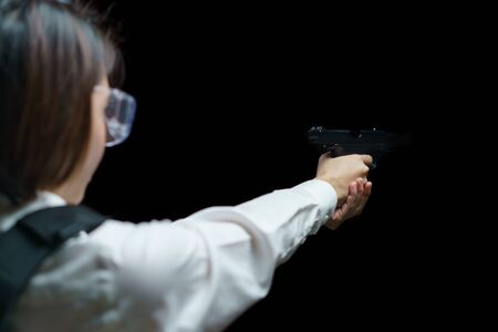 Woman wearing bulletproof vest shoots with gun at a target at indoor gun range. Banque d'images