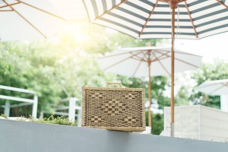 A wicker suitcase near the pool.