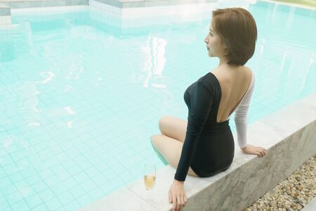 Woman in black and white swimsuit sitting by the poolside and drinking champagne.