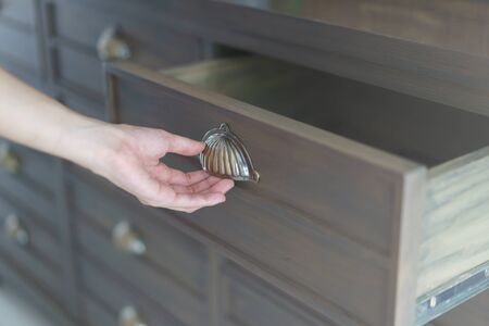 Hand opening brown wooden filing cabinets drawers. Archivio Fotografico - 150370923