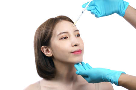 Hands of beautician injecting Botulinum Toxin A to asian woman in eye area. Stockfoto