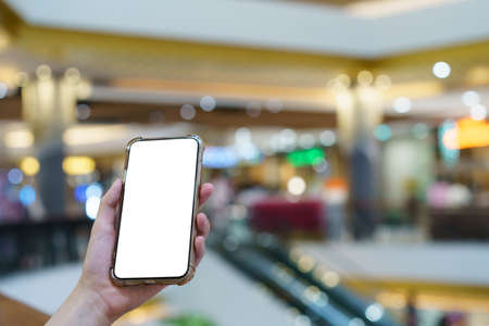 Mockup, hands holding blank white screen mobile phone in blurred department store, digital payment concept