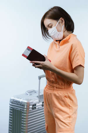 Woman wearing face mask, holding luggage passport and boarding pass, new normal travel concept.(Fake barcode)