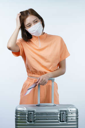 Woman take off her face mask her holding passport and boarding pass, new normal travel concept.(Fake barcode) Imagens