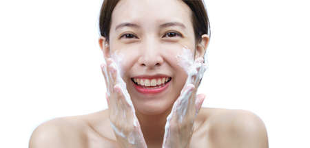 Asian woman wash her face with bubble cleansing foam isolated on white background. Archivio Fotografico