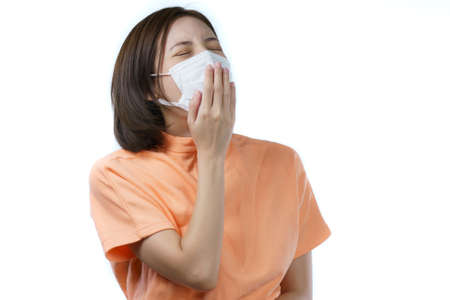 Woman wearing protective mask yawning and covering mouth with hand.