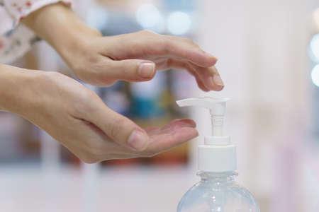 Woman hand press sanitizer bottle to clean her hand. hygiene prevention of coronavirus (Covid-19) virus outbreak.