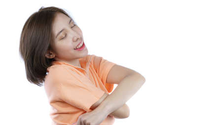 woman taking off her orange shirt, side view. White background. Archivio Fotografico